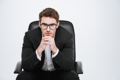 Young pensive business man in eyeglasses sitting on a chair
