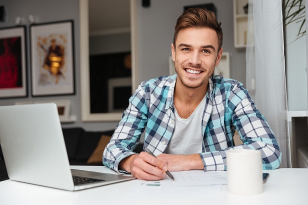 graphicstock-image-of-joyful-bristle-man-dressed-in-shirt-in-a-cage-print-sitting-in-home-and-using-laptop-computer-while-writing-notes-for-analyzing-home-finances_SIZYvwXd3g.jpg